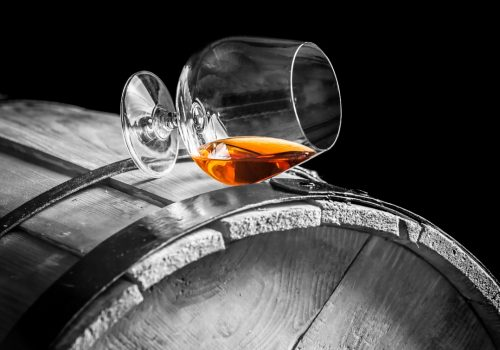 Glass of cognac on the vintage barrel.