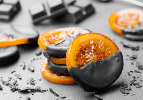 Candied orange slices in chocolate. Slate background.